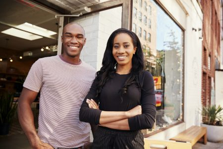 Young couple smiling to camera outside their clothes shop